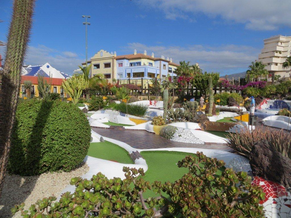 En stor fin golfbana med trädgårdsplanteringar.