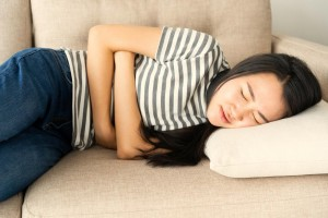 woman-on-a-sofa-holding-her-stomach-due-to-stomach-pain-and-nausea